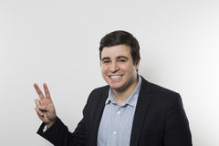Studio shot of happy businessman showing peace Royalty Free Stock Photos