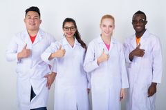 Studio shot of happy diverse group of multi ethnic doctors smili. Ng while giving thumb up together royalty free stock photography