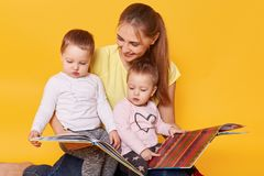Studio shot of happy family: mother and little twins girls sitting on floor, reading books and viewing bright interesting pictures royalty free stock image