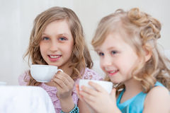 Studio shot of happy little girls drinking tea Stock Image