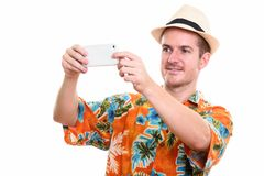 Studio shot of happy man smiling while taking picture with mobil. E phone stock photography