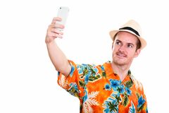 Studio shot of happy man smiling while taking selfie picture wit. H mobile phone stock image