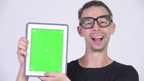 Studio shot of happy nerd man showing digital tablet