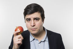 Studio shot of happy person eating an apple Royalty Free Stock Photos