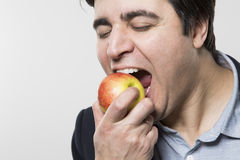 Studio shot of happy person eating an apple Royalty Free Stock Photo