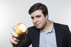 Studio shot of happy person eating an apple Royalty Free Stock Photography