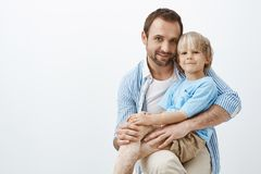 Studio shot of happy positive father and son with vitiligo, hugging and smiling broadly at camera, being pleased and stock photos