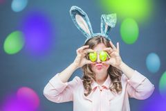 Studio shot of a happy young woman wearing bunny ears and holding up a colorful Easter egg in front of her eye royalty free stock image