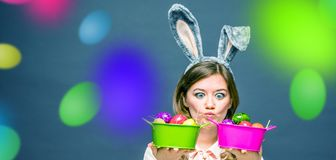 Studio shot of a happy young woman wearing bunny ears and holding up a colorful Easter egg in front of her eye royalty free stock photo