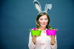 Studio shot of a happy young woman wearing bunny ears and holding up a colorful Easter egg in front of her eye stock photo