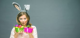 Studio shot of a happy young woman wearing bunny ears and holding up a colorful Easter egg in front of her eye royalty free stock photography