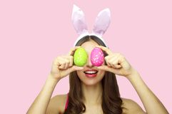 Studio shot of a happy young woman wearing bunny ears and holding up a colorful Easter eggs in front of her eyes isolated on pink royalty free stock image