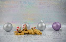 Christmas food photography gingerbread man mini music santa claus and silver tree baubles on xmas wrapping paper background Stock Images