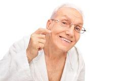 Studio shot of a joyful senior checking his skin Royalty Free Stock Photos
