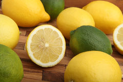 Studio shot of lemons and limes on wooden pad Stock Images