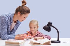 Studio shot of little charming girl sits at table, has difficult homework task, her mother trying to help daughter and explains. Mathematics rules, uses reading royalty free stock photography