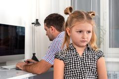 Studio shot of a little girl and her father.  The daughter takes offense at her father, because he gives her little time for games royalty free stock photo