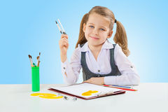 A little girl at shool table. Studio shot Royalty Free Stock Images