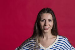 Studio shot of a lovely beautiful woman against an empty red studio wall stock photo