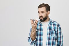 Studio shot of male european adult holding phone near mouth while talking to it on speaker, standing against gray. Background. Person enters note in his Royalty Free Stock Photos