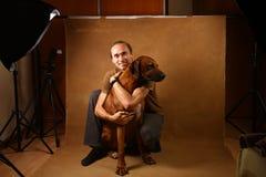Studio shot of a man with Rhodesian Ridgeback Dog on brown Background stock photo