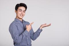 Studio shot of a man`s hand pointing at something. Shot Stock Image
