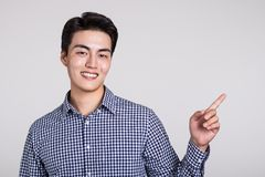 Studio shot of a man`s hand pointing at something. Shot Stock Photo