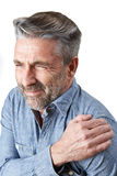 Studio Shot Of Man Suffering With Frozen Shoulder. Man Suffering With Frozen Shoulder stock photo