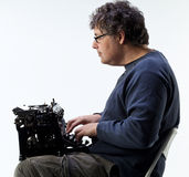 Studio shot of a man typing with the typewriter on his lap Royalty Free Stock Photos