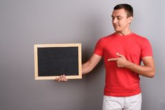 Man wearing red shirt against gray background. Studio shot of man wearing red shirt against gray background Stock Photos