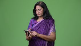 Mature beautiful Indian woman using phone. Studio shot of mature beautiful Indian woman wearing traditional clothes against chroma key with green background stock video footage