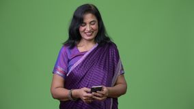 Mature happy beautiful Indian woman using phone. Studio shot of mature beautiful Indian woman wearing traditional clothes against chroma key with green stock video footage