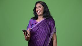 Mature happy beautiful Indian woman using phone. Studio shot of mature beautiful Indian woman wearing traditional clothes against chroma key with green stock video
