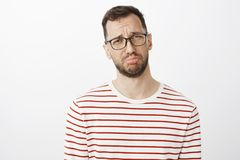 Studio shot of mature gloomy man with beard in glasses, pouting and crying, complaining to friend about boyfriend who. Forgot about anniversary, standing upset royalty free stock image