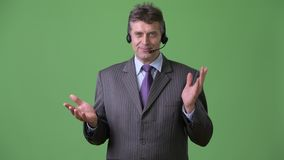 Mature handsome businessman against green background