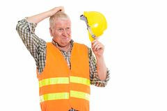 Studio shot of mature man. Construction worker thinking while scratching head and holding safety helmet royalty free stock photos