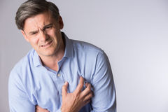 Studio Shot Of Mature Man Suffering Heart Attack Stock Image