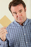 Studio Shot Of Middle Aged Man Holding Wage Packet Royalty Free Stock Image
