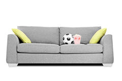 Studio shot of a modern couch with soccer ball and popcorn box o Royalty Free Stock Photography