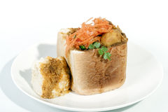 Studio Shot Mutton Curry Bunny Chow and Sambles. Studio shot traditional South African mutton bunny chow and carrot sambles Stock Image
