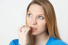 Studio Shot Of Nervous Woman Biting Nails royalty free stock image