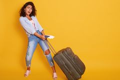 Studio Shot Of Beautiful Girl Carries Heavy Suitcase With Documents And Flight Tickets In Hand, Posing With Opened Mouth, Looks Royalty Free Stock Photography