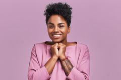 Free Studio Shot Of Cheerful African American Female Keeps Hands Together Near Chin, Smiles Broadly, Anticipates For Surprise Stock Photos - 131556193
