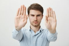 Free Studio Shot Of Handsome Serious Young Man In Ordinary Clothes Pulling Palms Towards Camera In Stop Or No Sign, Declining Stock Image - 112346821