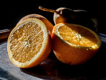 Studio shot of orange and pear. Studio shot of orange cut in half with pears in the back ground light coming through the window royalty free stock photo
