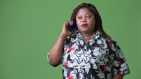Overweight beautiful African woman against green background. Studio shot of overweight beautiful African woman against chroma key with green background stock video