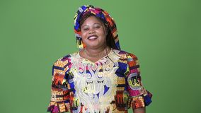 Overweight beautiful African woman wearing traditional clothing against green background stock video footage