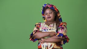 Overweight beautiful African woman wearing traditional clothing against green background. Studio shot of overweight beautiful African woman wearing traditional stock video