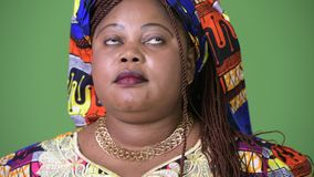 Overweight beautiful African woman wearing traditional clothing against green background. Studio shot of overweight beautiful African woman wearing traditional stock video footage