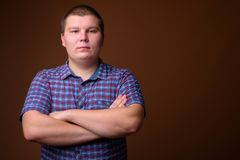 Studio shot of overweight young man against brown background royalty free stock photos